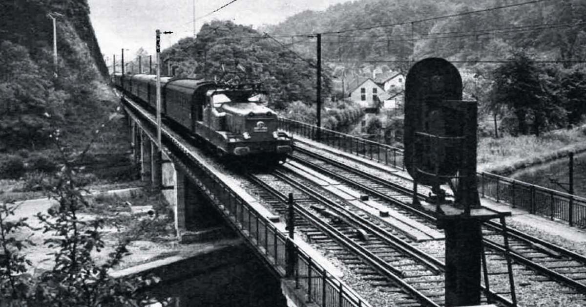 Un train de voyageurs, remorqué par une locomotive électrique, franchit le canal de la Marne au Rhin, près de Saverne.