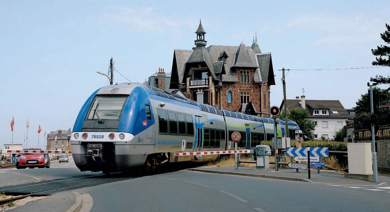 À Houlgate, franchissement d'un PN de type SAL 2 par l'AGC X 76527/28 assurant un train entre Dives-Cabourg et Trouville-Deauville (16 juillet 2015). (c) MARC CARÉMANTRANT