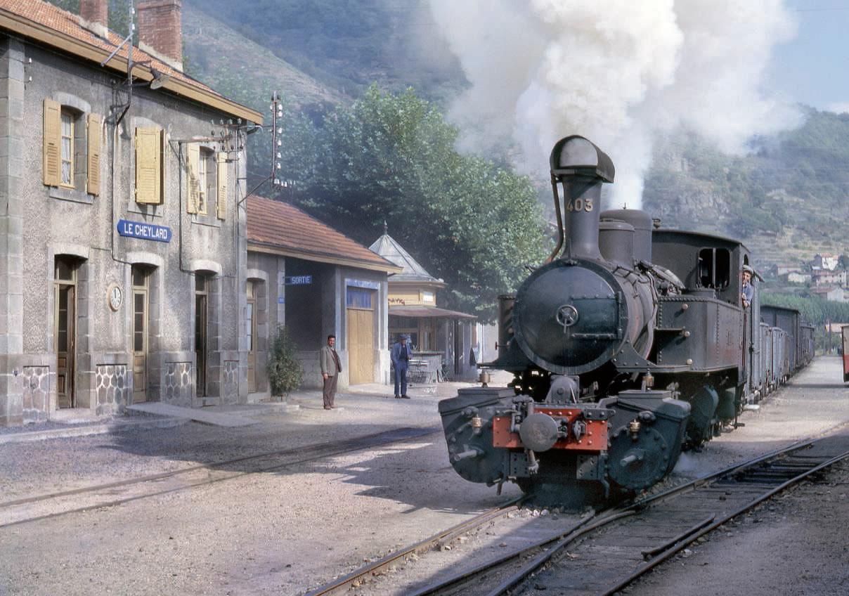 dans un panache de vapeur généreux, la Mallet 403, dont la cheminée est recouverte d'une grille pare-escarbilles, une situation classique sur les CFD du Vivarais, quitte la gare du Cheylard le 9 octobre 1962 avec le train de marchandises pour Dunières. En arrièreplan, le long du BV, se dresse la charmante petite buvette de la gare.